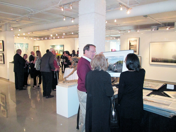 Guests discuss Charles Jacobs work with art consultants while perusing the extensive collection of photographs
