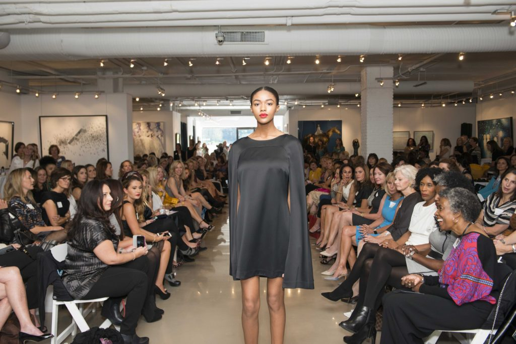 One of the models wearing a caped dress, previewing fall fashion trends
