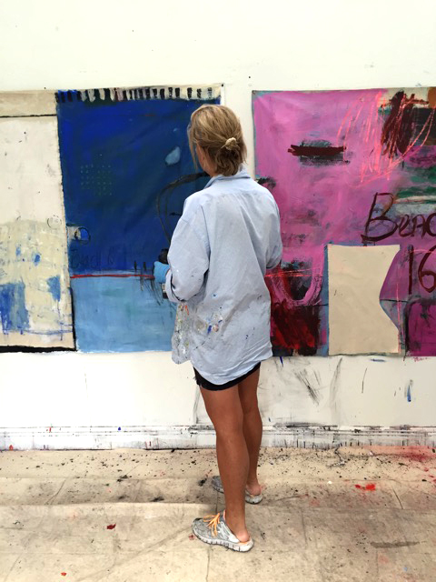 Andrews working in the studio in front of two canvas works in progress