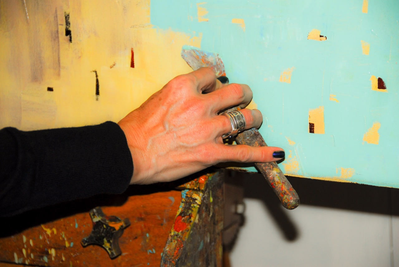 The artist layering a new color on top of underpainting, while leaving traces behind as a layering technique