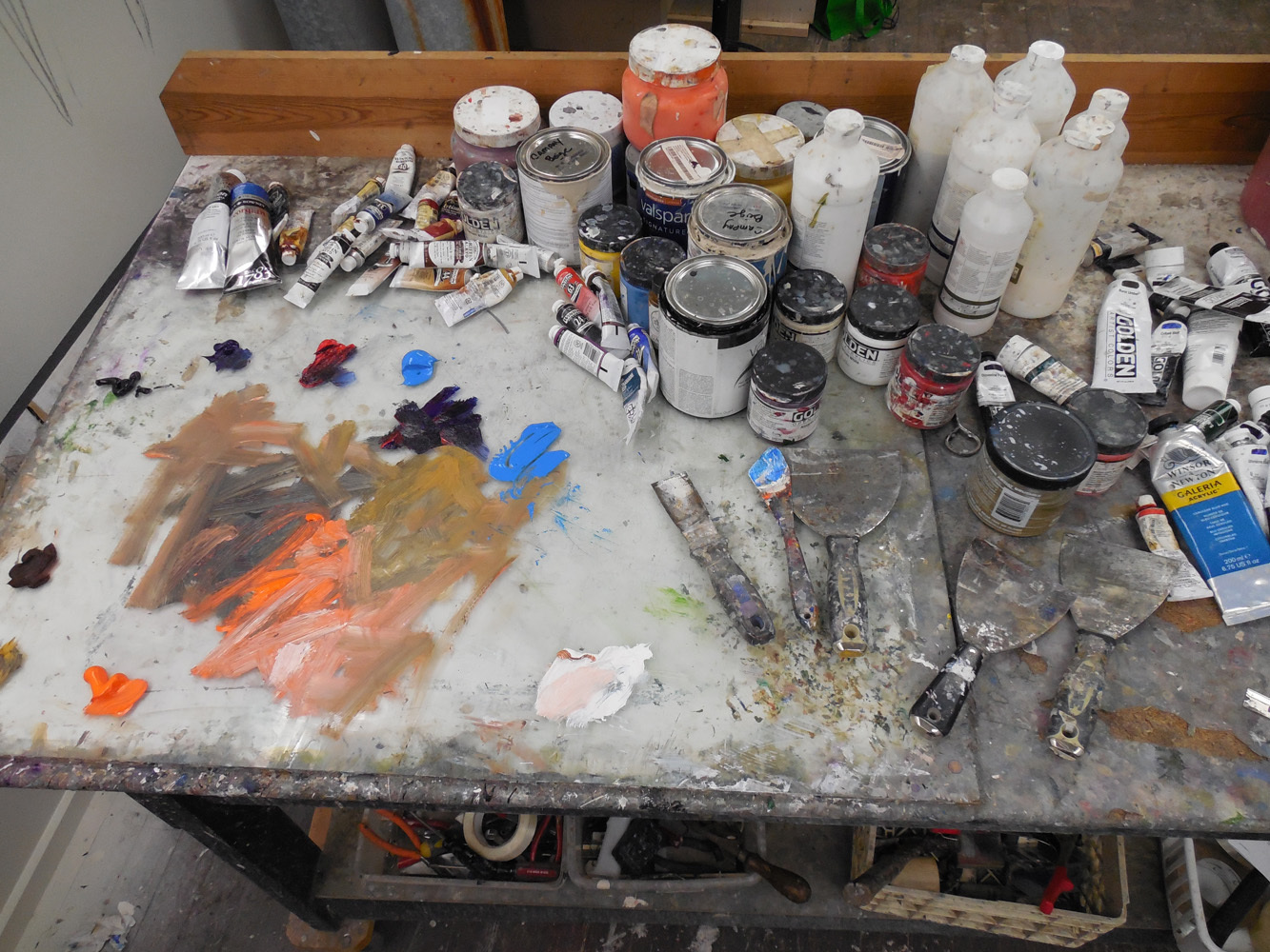 I come in everyday to my studio. I have a moderate 500 square foot space with cathedral ceilings about 12ft high. I have a long wall that I painted a mural on. I have a box that I built on rollers which can handle a lot of the taller pieces. It's a very physical work space. I have palate knives that I get from Home Depot or Lowes. I buy a lot of the tools from hardware stores. When people look at my work they can feel how physical it is. Very labor intensive projects that relay on a lot of different materials. I do 6 to 8 paintings at a time. I like to walk a semi-circle around my work. I want to have something to catch the viewer from every angle. I adjust things through this process. I want it to be enjoyed from all perspectives rather than just the face. In a lot of ways my paintings are sculptural